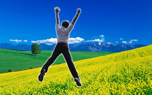 お花畑でジャンプする男性