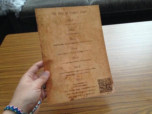 ルール オブ 絶品クラブと書かれた紙を持つ人
