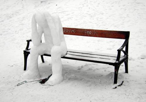 ベンチに座り頭をかかえる人