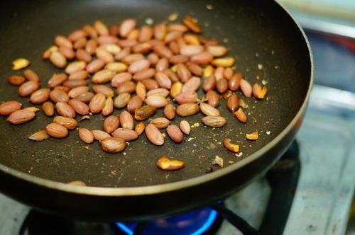 殻を割ってフライパンで煎られる落花生
